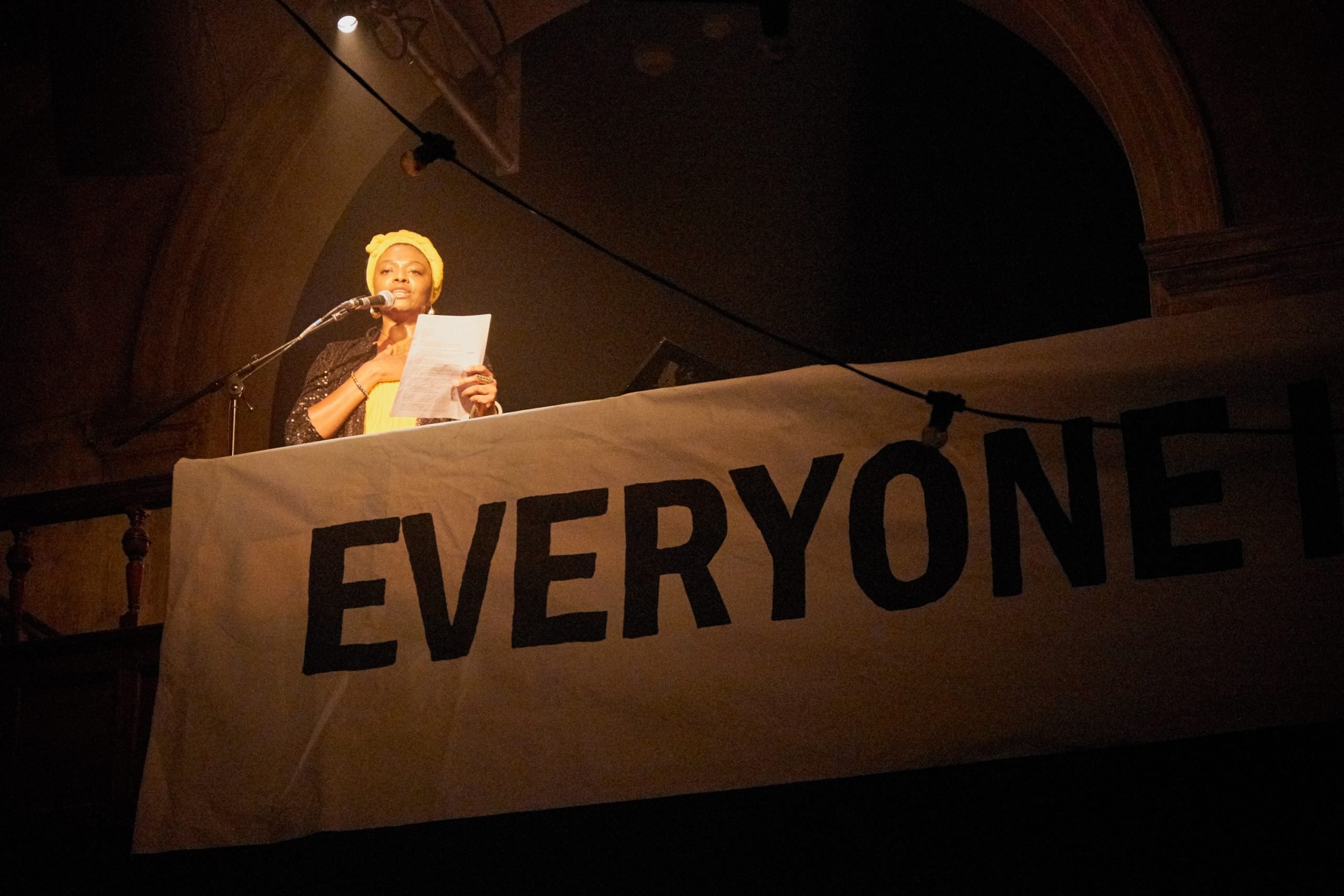 Picture of poet Zena Edwards standing in front of a banner which reads 'Everyone'.