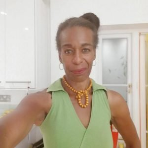 A woman in a green sleeveless top and yellow beaded necklace with her hair in a bun smiles at the camera