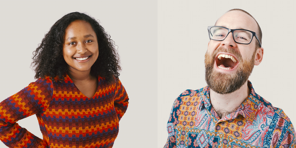 A woman in a stripy orange and red jumpey, and a laughing man in glasses