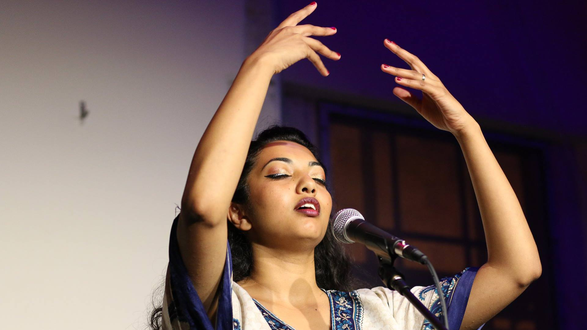A woman with tied back dark hair and painted lips, raises her arms whilst speaking into a mic on stafe