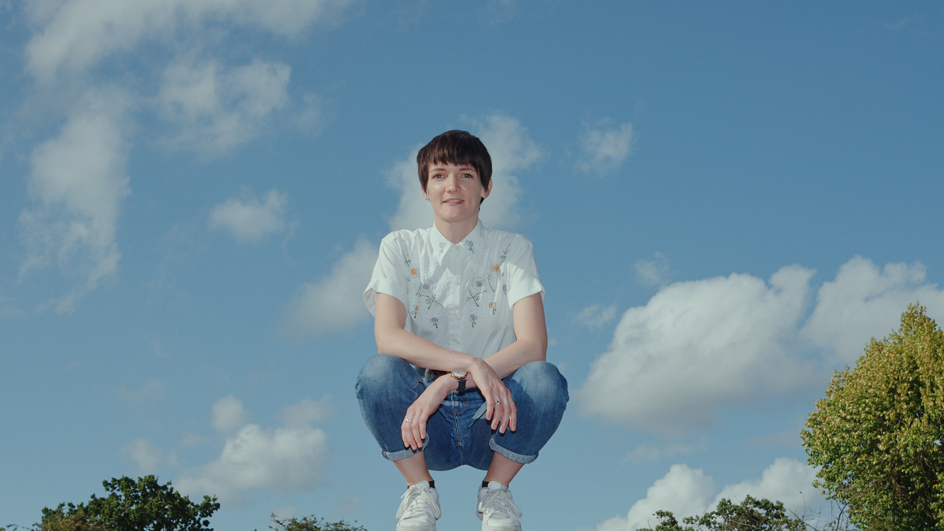 A woman with short hair, white shirt and blue jeans squats on a brick wall against a blue sky