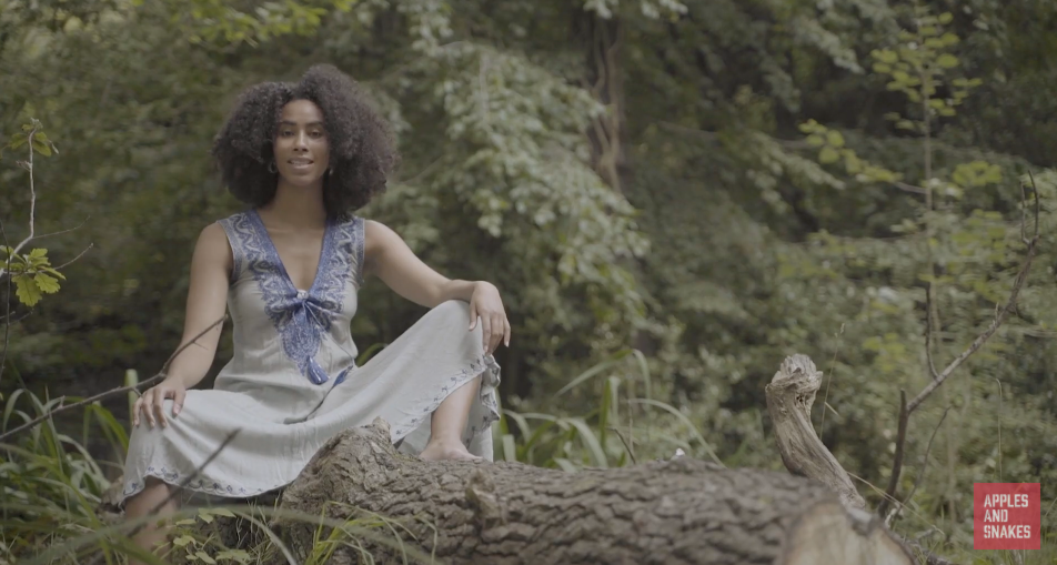 Screenshot of 'With You I See Light', a poetry film by Aisha Sanyang-Meek. It shows Aiysha with her hair loose, sitting in a forest. Her pose is strong.