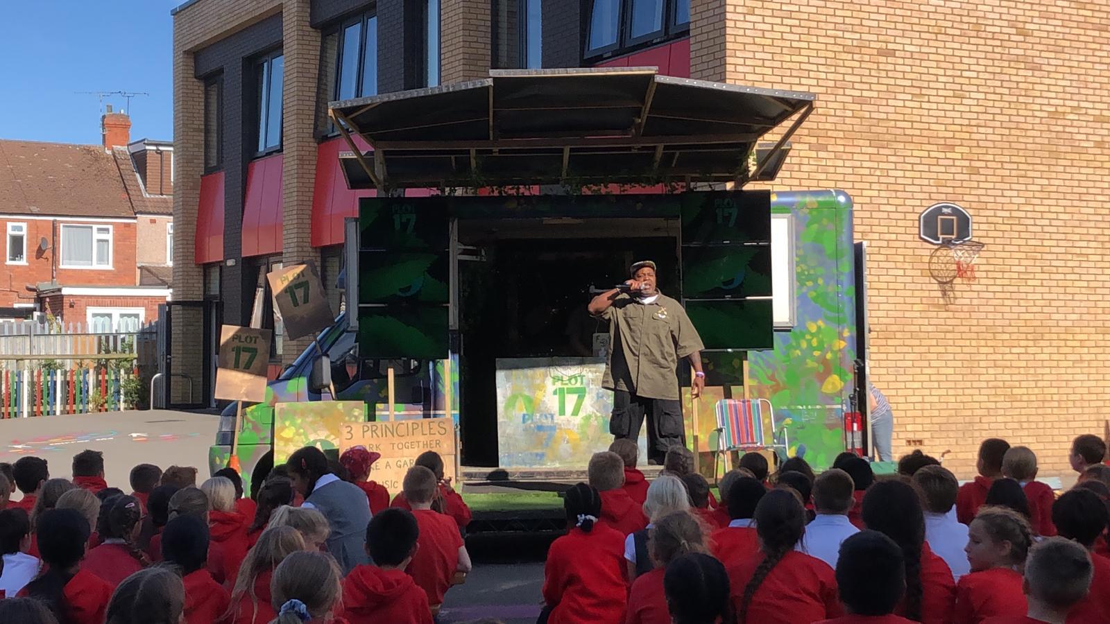 Photo of primary school children listening to a performance of Plot 17 by Kenny Baraka